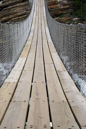 Suspension bridge made of wooden planks and stainless steel cables