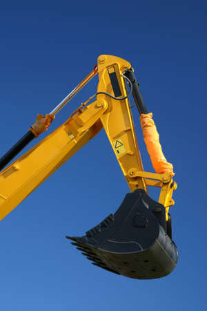 Black digging bucket on the end of a yellow hydraulic arm of a digging machine