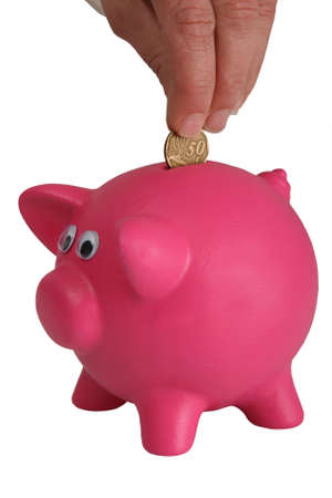 Pink piggy bank and hand inserting a money coin photo