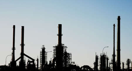 Silhouette of an oil refinery with pipes and chimneys photo