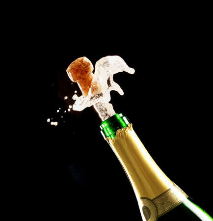Bottle of champagne just opened with cork being expelled photo