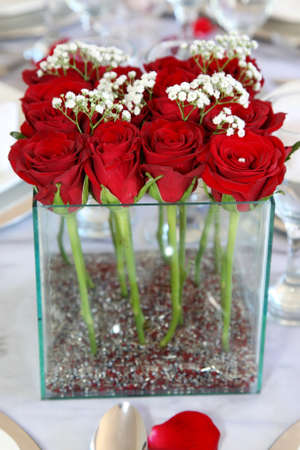 Red roses arranged in a square vase on a wedding table