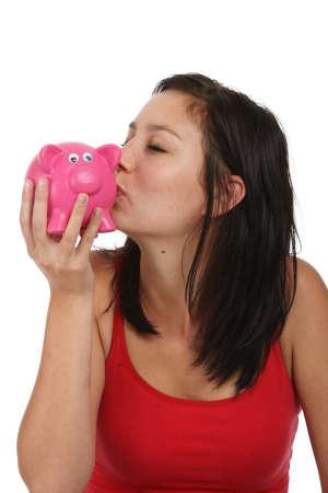 Pretty brunette woman kissing a pink piggy bank photo