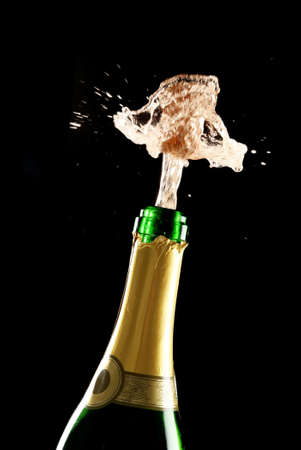 Champagne bottle with cork bursting out and spray photo