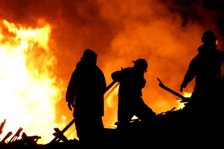 Three fireman in silhouette fighting a raging fire Stock Photo