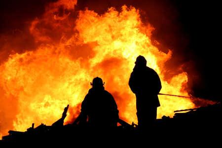 Zwei silhouetted Feuerwehrmänner, die Kämpfe eines Großbrand