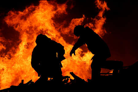 Two silhouetted firemen fighting a large fire Stock Photo - 8604906