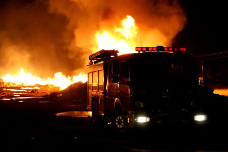 A firetruck in front of a blazing fire at night
