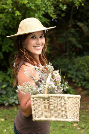 Gorgeous young lady doing gardening and holding a basket of cut flowers Stock Photo - 8756914