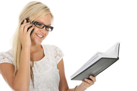 Beautiful young blond woman talking on mobile phone and checking her diary photo