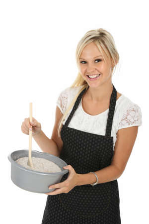 Gorgeous blond woman in apron with cooking bowl and spoon photo
