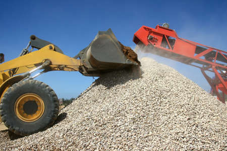 Front end loader and conveyor belt on a pile of graded stone Stock Photo