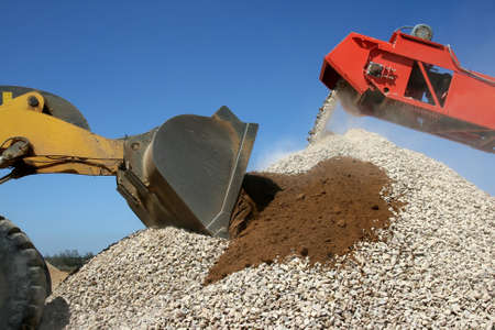 front end: Front end loader and conveyor belt on a pile of graded stone Stock Photo