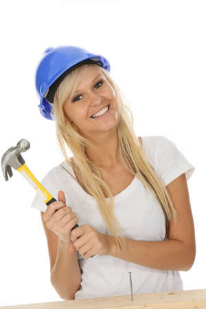 Gorgeous blond woman hammering a nail into wood photo