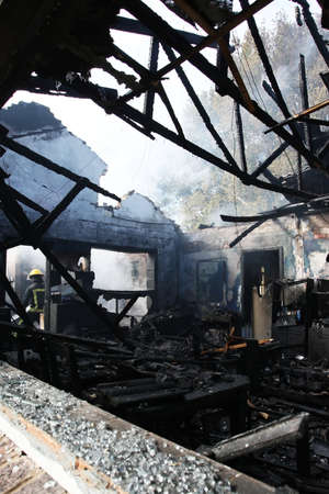 fire damage: Burnt out house with charred roof trusses and burnt furniture Stock Photo