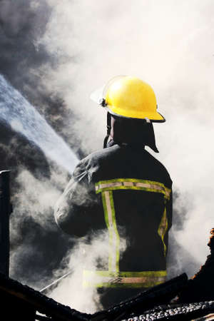Fireman spraying water in a smouldering burnt out house photo