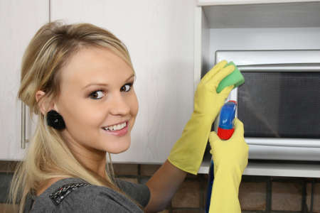 Lovely blond housewife wearing yellow gloves and cleaning the kitchen photo