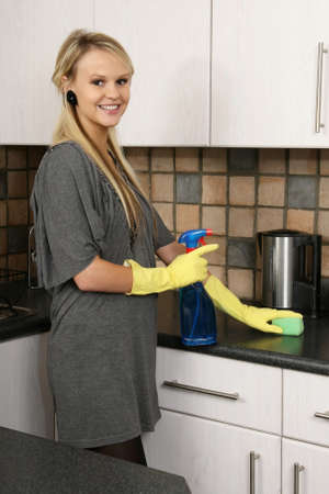 Lovely blond housewife wearing yellow gloves and cleaning the kitchen Stock Photo - 9768976