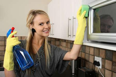 microondas: Encantadora ama de casa rubia con guantes amarillos y su cocina de limpieza
