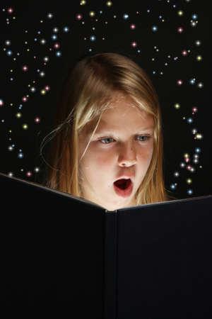 Chica muy joven escuela absorto en la lectura de un libro con estrellas saliendo de ella Foto de archivo - 9827833