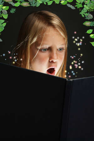 Pretty young school girl engrossed in reading a book with stars coming out of it photo