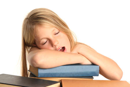 Little girl yawning and falling asleep on her books photo