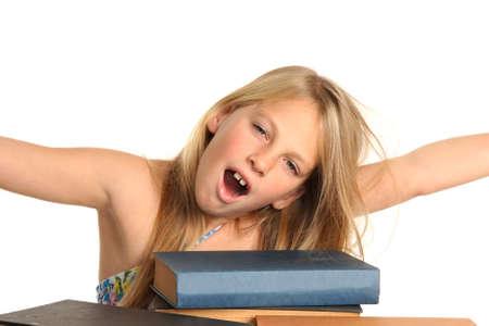 yawing: Chica rubia bastante preadolescente orient�ndose y estiramientos con pila de libros delante de ella Foto de archivo