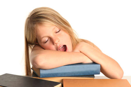 Little girl yawning while resting on her books photo