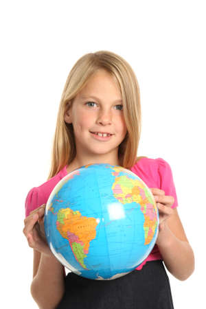 Cute and confident young preteen girl holding the world globe in her fingers Stock Photo