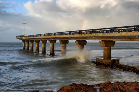 Pier jutting out into the stormy sea and a small rainbow in the clouds photo