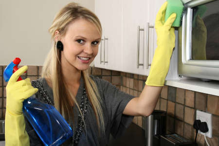 Lovely smiling blond lady cleaning her kitchen photo