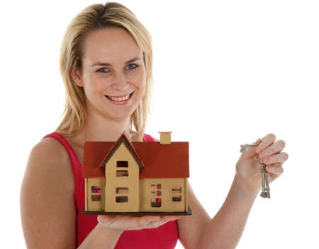 Pretty young blond estate agent sales lady holding out a model house and keys Stock Photo - 10216616