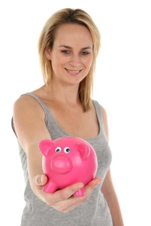 Pretty blonde girl holding a pink piggy bank photo