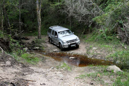 4x4: Offroad 4x4 vehicle at a stream in the wilderness