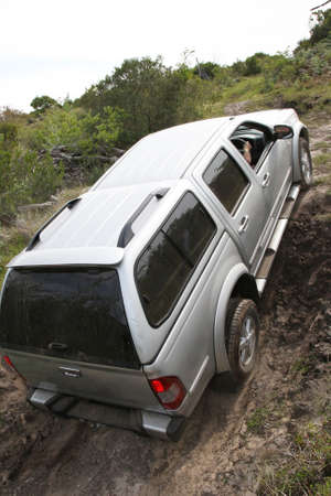 An offroad 4x4 vehicle negotiang a steep climb Stock Photo
