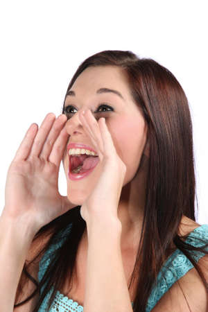Pretty brunette woman with hands cupped to mouth and shouting