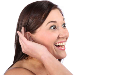 audible: Lovely brunette woman with excited expression and hand cupped to her ear