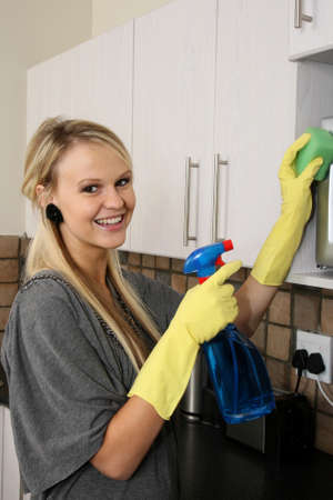 housewife gloves: Lovely smiling blond lady cleaning her kitchen Stock Photo