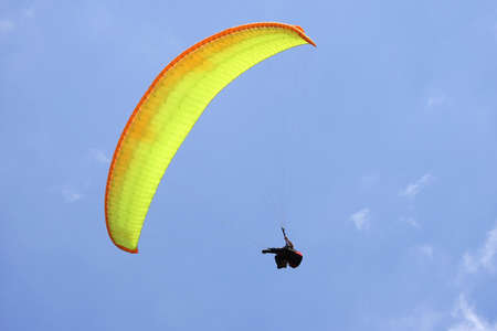 parasailing: Orange and yellow parasail gliding in the blue sky Stock Photo