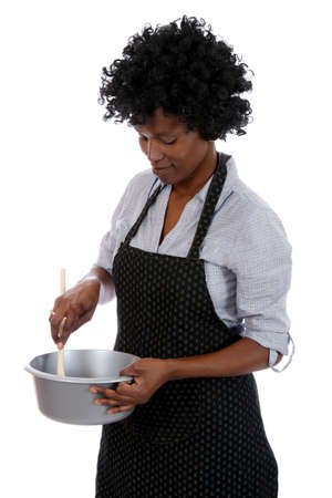 African woman with curly black hair stirring a cooking mixture in a pot photo