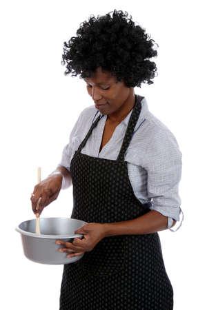 mujeres cocinando: Mujer africana con el cabello negro y rizado agitando una mezcla de cocina en una olla
