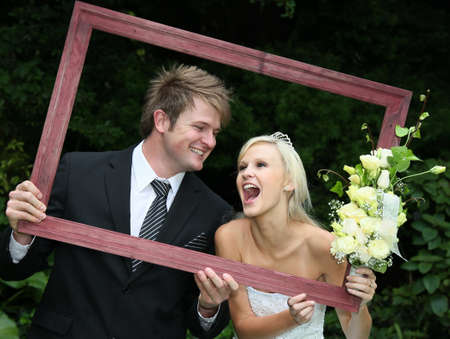 Lovely laughing wedding couple looking through a wooden picture frame Stock Photo