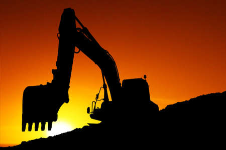 Silhouette of a digging machine at sunset photo