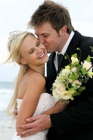 Pretty blond bride and her groom at the sea shore photo