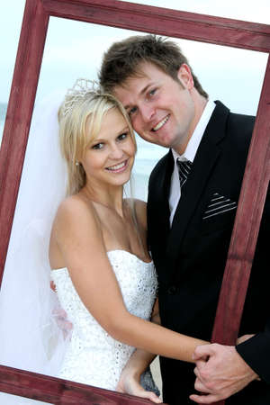 bridal couple: Lovely wedding couple looking through a picture fram