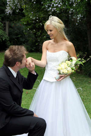 Handsome groom kneeling to kiss his beautiful brides hand photo