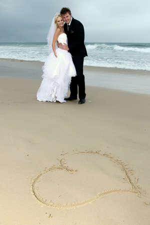 Pretty blond bride and her handsome groom at the sea shore Reklamní fotografie - 11962421