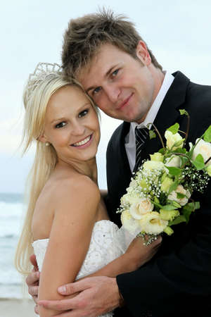 Pretty blond bride and her handsome groom at the sea shore