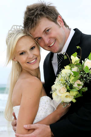 Pretty blond bride and her handsome groom at the sea shore photo