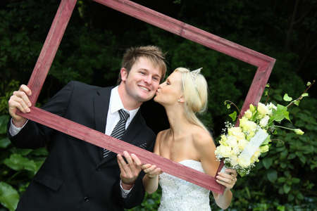 picture person: Lovely wedding couple looking through a picture fram